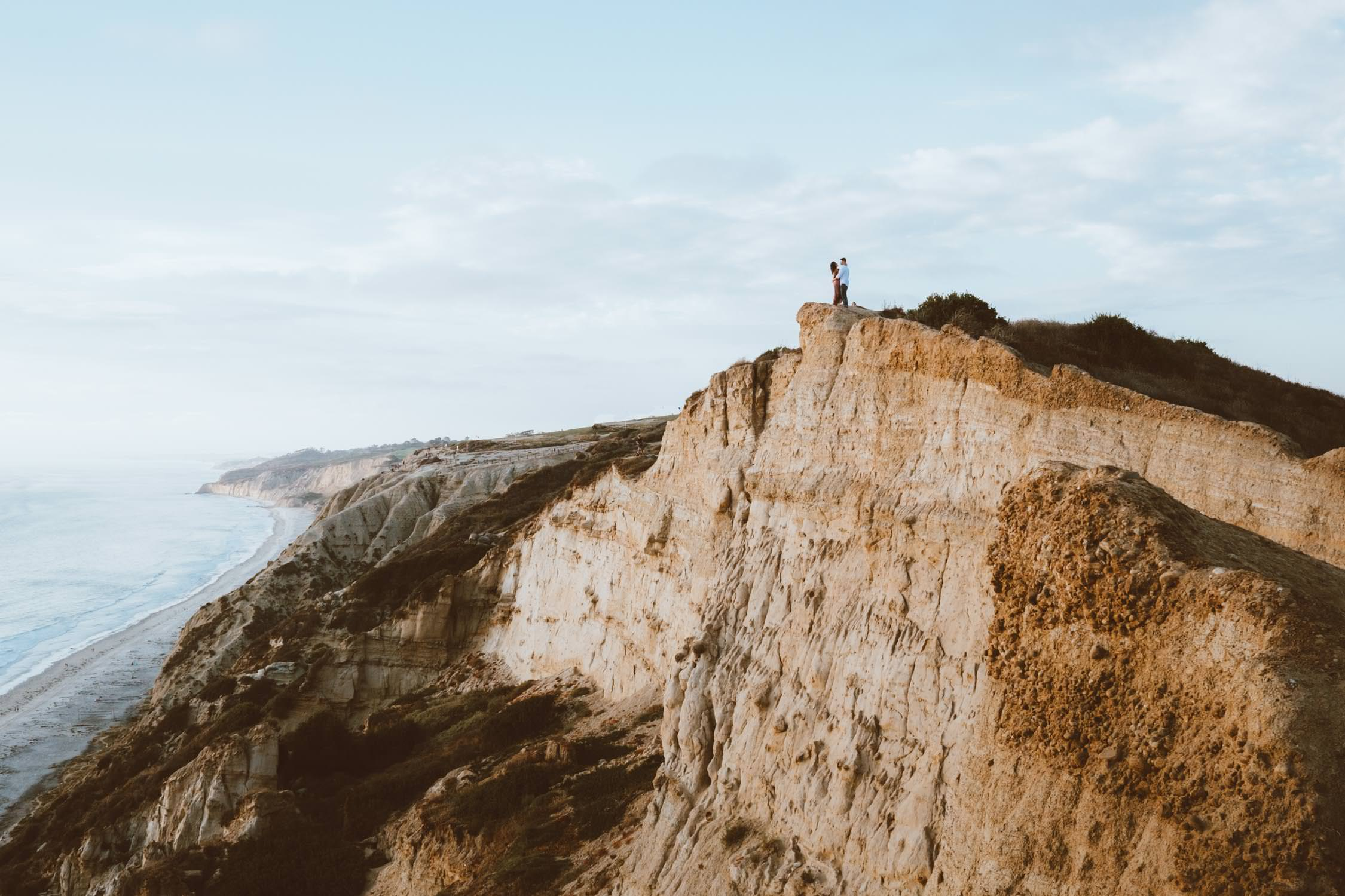 adventurous couple hiking barefoot for engagement session la jolla 32