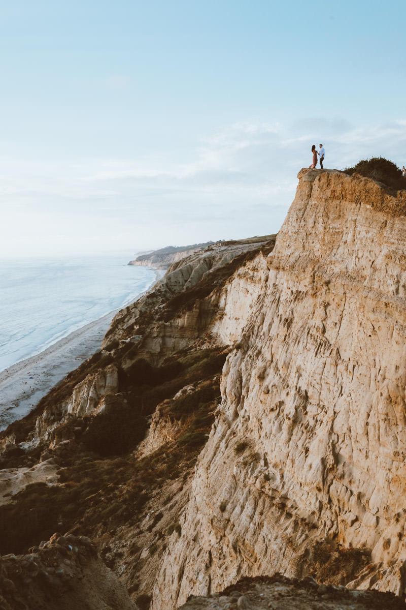 adventurous couple hiking barefoot for engagement session la jolla 11