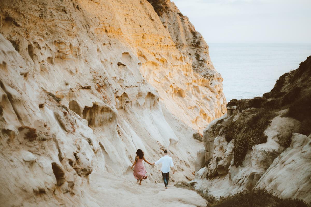 adventurous couple hiking barefoot for engagement session la jolla 15