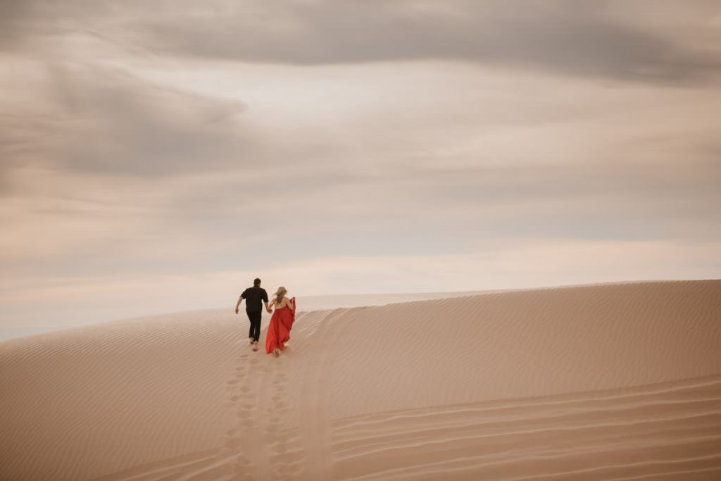 glamis sand dunes engagement session running towards the sun