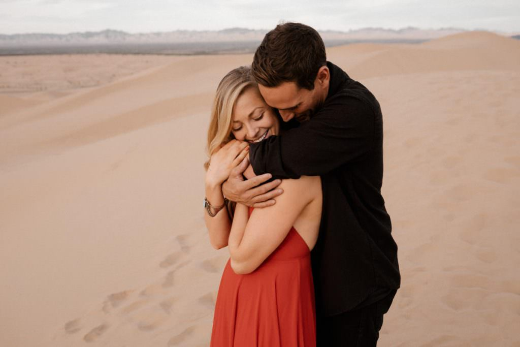 glamis sand dunes engagement session a hug from behind