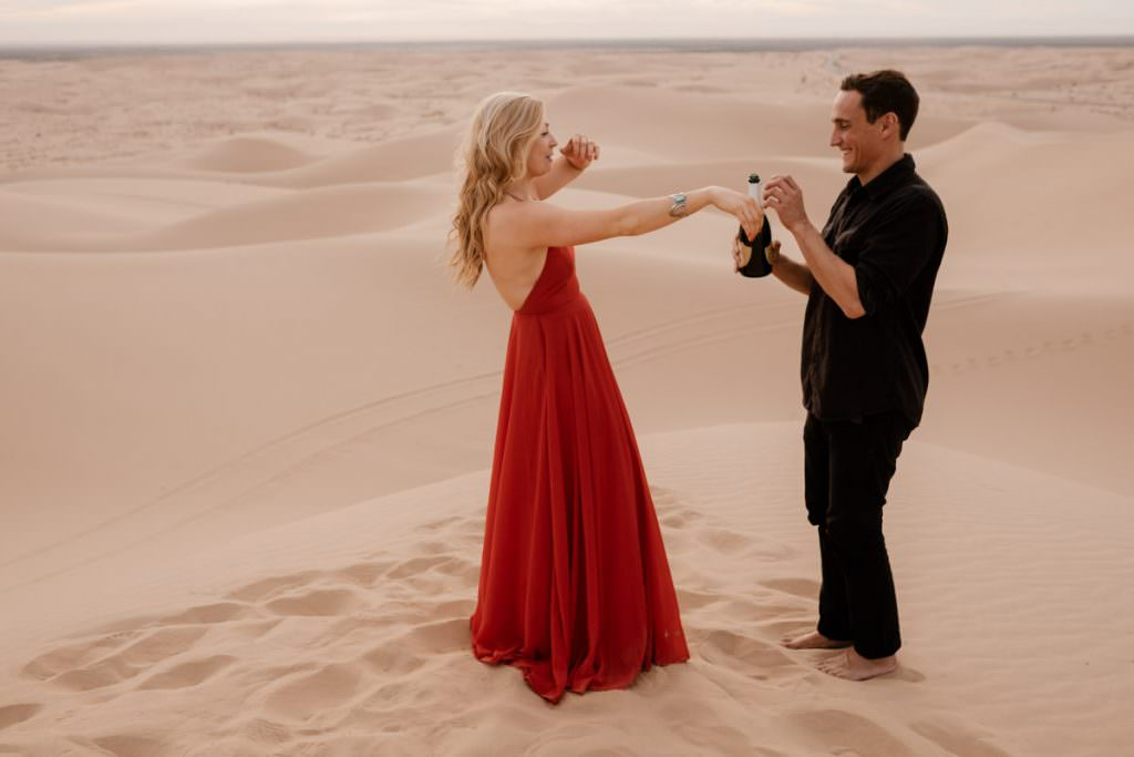 glamis sand dunes engagement session sharing a sip of champagne