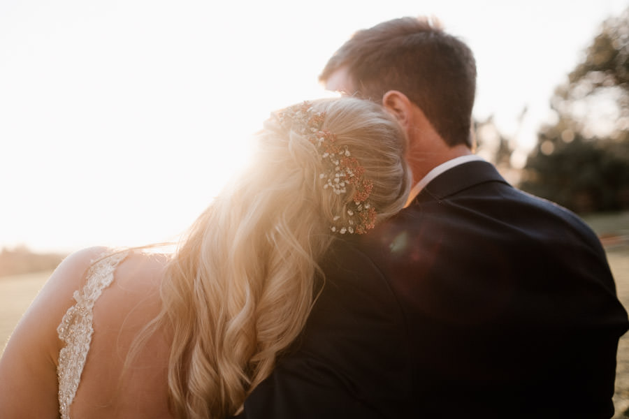 bride leaning on grooms shoulder with the sun beaming on them