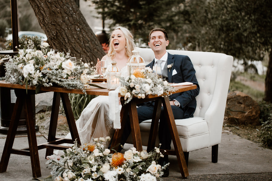 bride and groom smiling hard during toasts