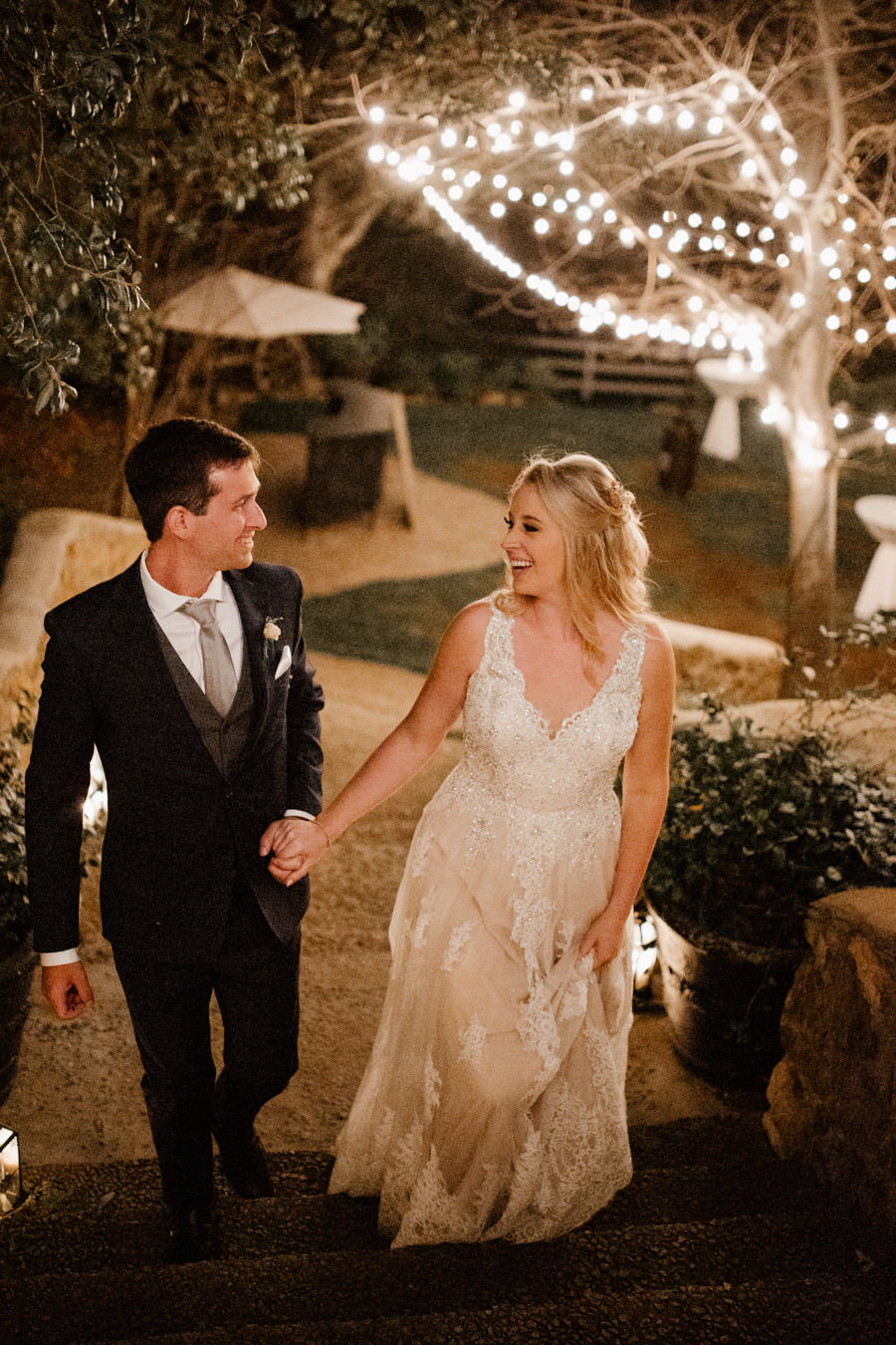moments in between bride and groom walking up the stairs with string lights on the back