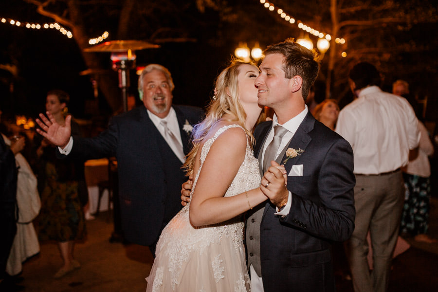 the couple sharing a sweet kiss with dad photobomb on the back