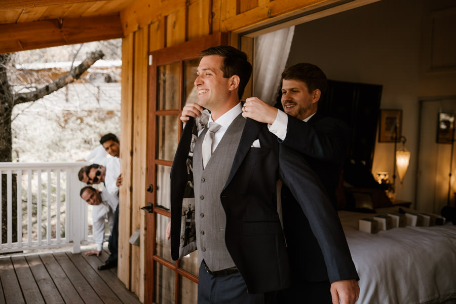best man helping groom put the jacket on
