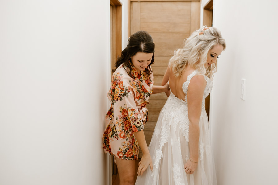 maid of honor helping bride with the dress