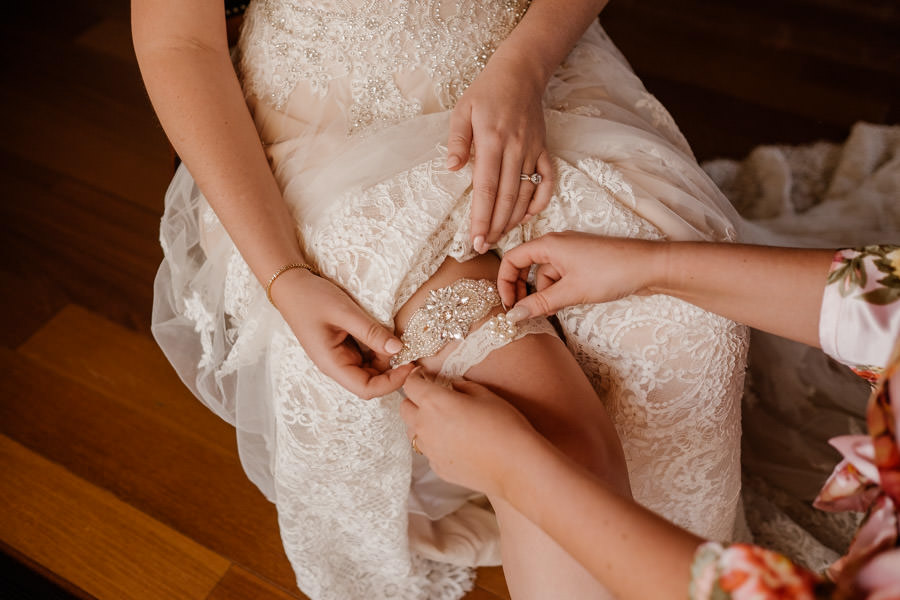 maid of honor helping bride putting the garters on