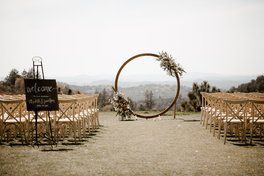 sacred mountain julian wedding ceremony with wooden arch and vintage chairs