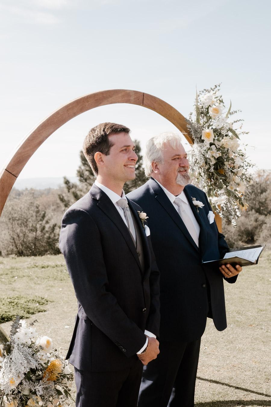 groom looking very happy seeing his bride down the aisle