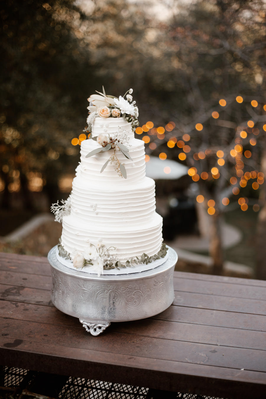wedding cake with beautiful string lights on the background