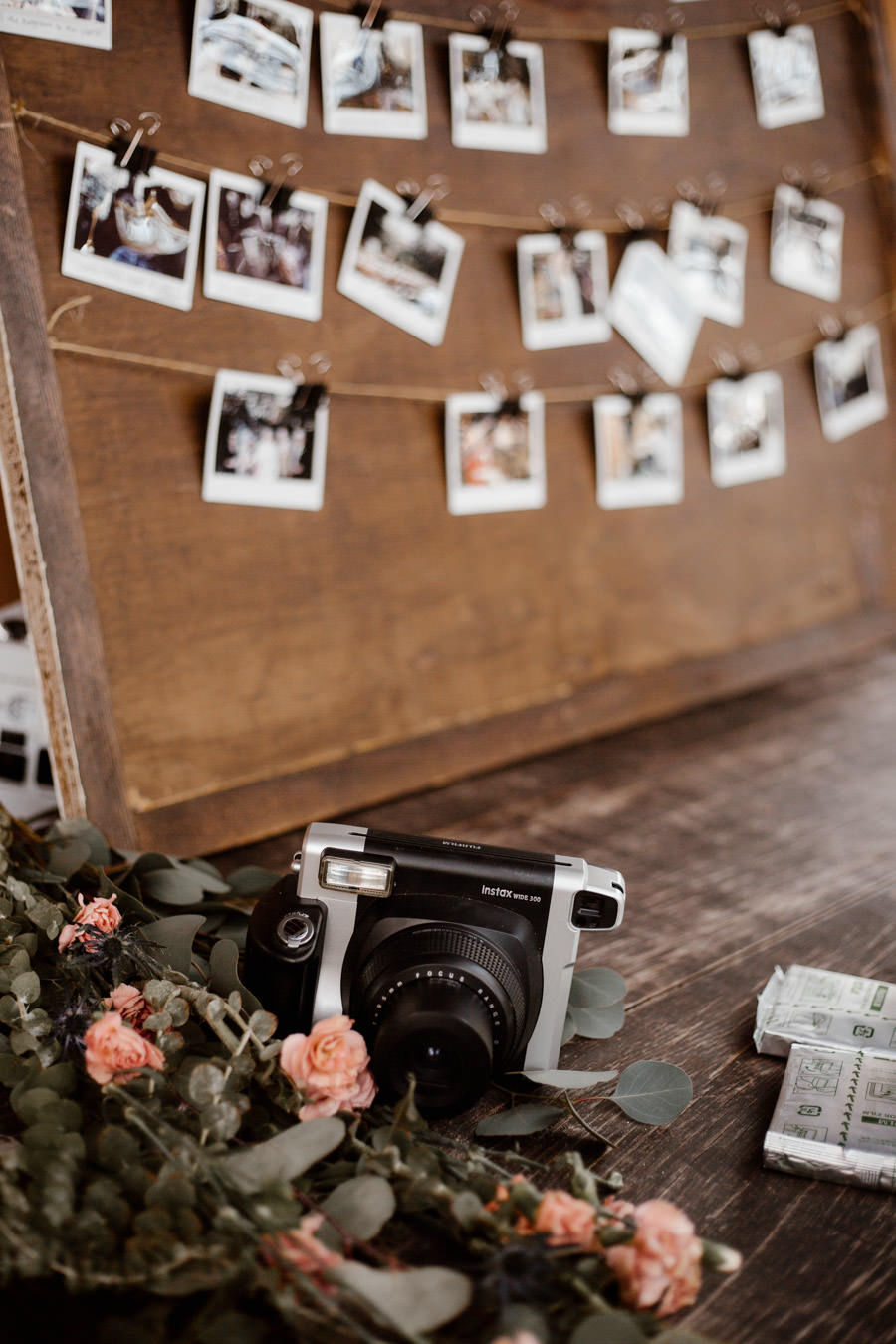 polaroid camera in front and a board full of photos on the background