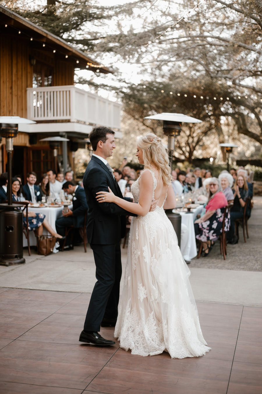 bride and groom first dance with loved ones on the background