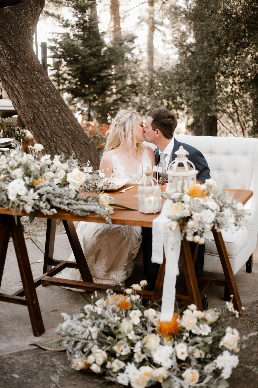 bride and groom sweet kiss at the sweetheart table