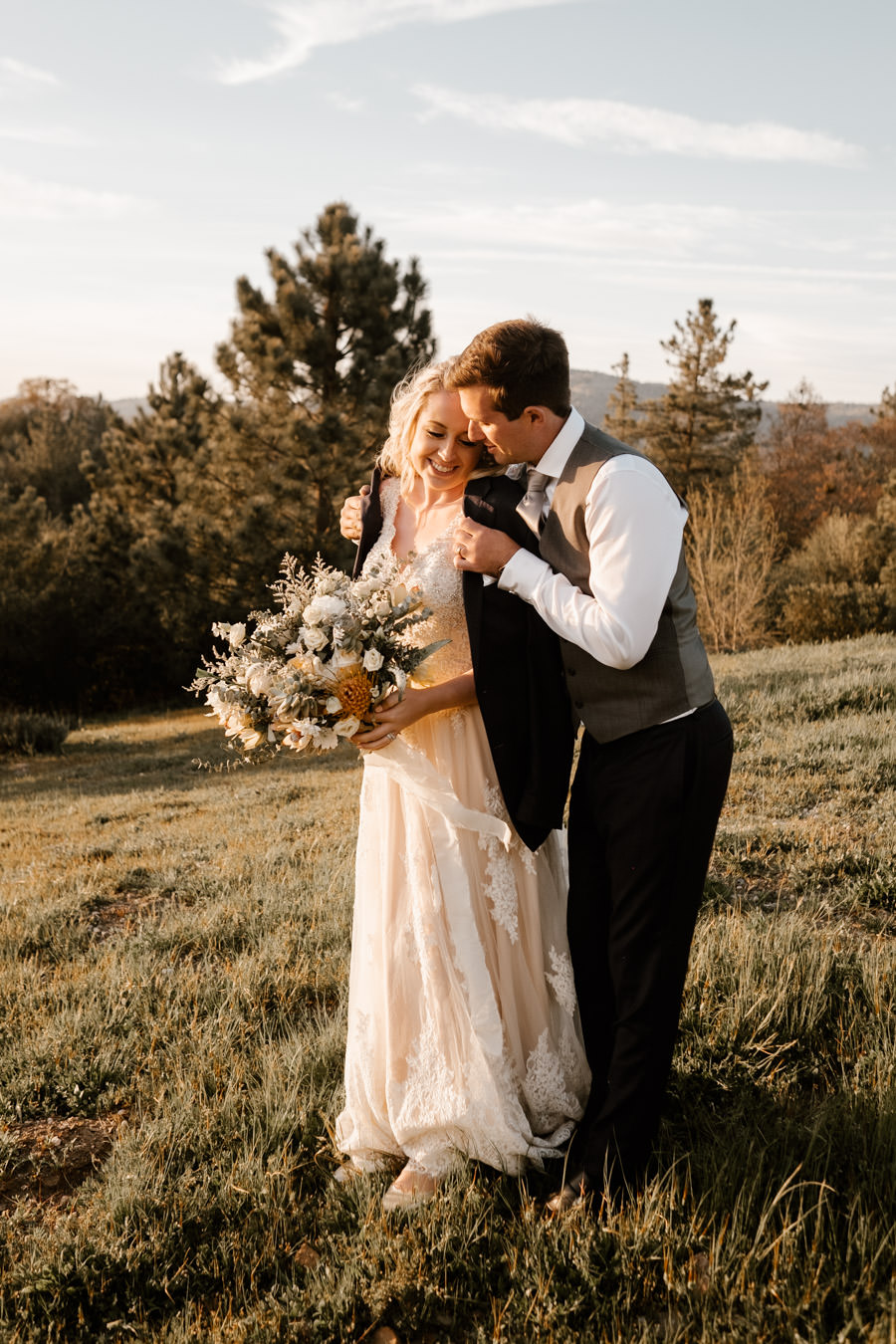 groom covering bride from the cold